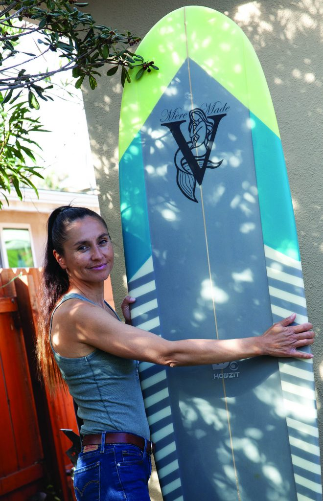 Valerie Duprat posing with a finished surfboard