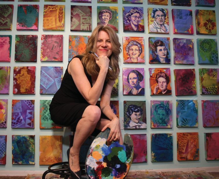 Veronica Funk posing sitting in front of her paintings